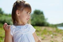 Portrait of merry little girl posing in park Stock Images
