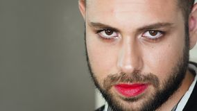 Portrait of metrosexual or gay man. Closeup portrait of metrosexual or gay man with bright red lipstick defiantly looking at the camera. Steam or powder in air stock video