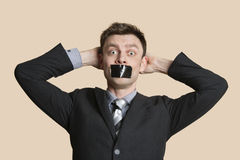 Portrait of a mid adult business professional staring with hands behind head and tape on mouth over colored background Royalty Free Stock Photos