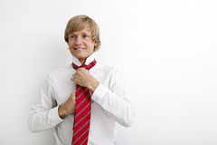 Portrait of mid adult businessman tying tie against white background Royalty Free Stock Image