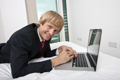 Portrait of mid adult businessman using laptop in bed at home Royalty Free Stock Image