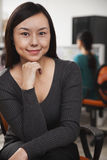 Portrait of mid adult businesswoman with hand on chin in the office Royalty Free Stock Photography