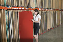 Portrait of mid adult businesswoman holding thin red veneer sheet Royalty Free Stock Photo