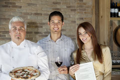 Portrait of mid adult chef holding pizza with young couple Royalty Free Stock Photo