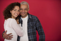 Portrait of a mid adult couple. Hugging on red background stock photography