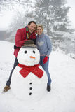 Portrait of mid adult couple with snowman.  royalty free stock image