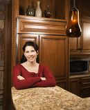 Portrait of mid-adult female in kitchen. Caucasian woman leaning on marble kitchen counter smiling with arms crossed and looking at viewer Stock Photography