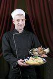 Portrait mid adult male chef in kitchen present Royalty Free Stock Images