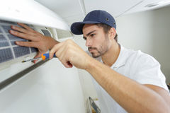 Portrait mid-adult male technician repairing air conditioner. Portrait of mid-adult male technician repairing air conditioner Stock Photos