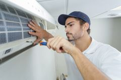 Portrait mid-adult male technician repairing air conditioner. Portrait of mid-adult male technician repairing air conditioner Stock Images