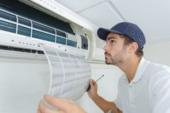 Portrait mid-adult male technician repairing air conditioner. Portrait of mid-adult male technician repairing air conditioner Royalty Free Stock Photos