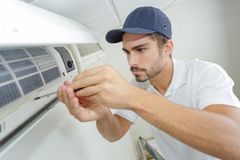 Portrait mid-adult male technician repairing air conditioner. Portrait of mid-adult male technician repairing air conditioner Stock Photo