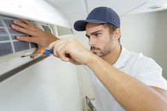 Portrait mid-adult male technician repairing air conditioner. Portrait of mid-adult male technician repairing air conditioner Stock Photography