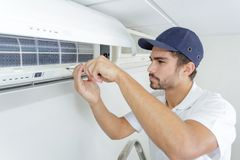 Portrait mid-adult male technician repairing air conditioner. Portrait of mid-adult male technician repairing air conditioner Royalty Free Stock Photo