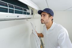 Portrait mid-adult male technician repairing air conditioner. Portrait of mid-adult male technician repairing air conditioner Royalty Free Stock Image