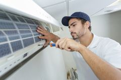 Portrait mid-adult male technician repairing air conditioner. Portrait of mid-adult male technician repairing air conditioner Royalty Free Stock Photography