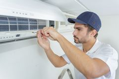 Portrait mid-adult male technician repairing air conditioner. Portrait of mid-adult male technician repairing air conditioner Royalty Free Stock Images