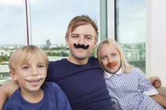 Portrait of mid adult man and children with artificial mustache at home Stock Photography