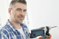 Portrait of mid-adult man drilling hole in wall stock photos