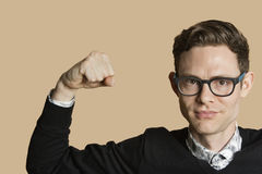 Portrait of a mid adult man flexing muscles over colored background Royalty Free Stock Photos