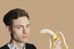 Portrait of a mid adult man holding banana over colored background Royalty Free Stock Photos