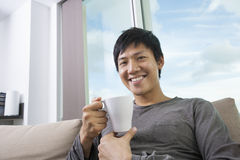 Portrait of mid adult man holding coffee cup in house Royalty Free Stock Image