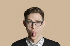 Portrait of a mid adult man sticking out tongue over colored background Royalty Free Stock Photography