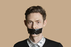 Portrait of a mid adult man with tape on mouth over colored background Stock Images