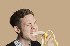 Portrait of a mid adult man winking while biting banana over colored background Stock Photography
