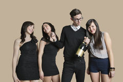 Portrait of mid adult man and young females holding champagne bottle over colored background Royalty Free Stock Photos