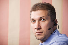 Portrait of mid adult operator worker. Portrait of mid adult man operator worker with headset looking at you,vertical blinds background copy space for text Stock Photos