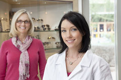 Portrait of a mid adult optometrist with female wearing glasses in background Royalty Free Stock Photos