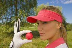 Portrait of a mid adult woman holding a golf ball.  Royalty Free Stock Images