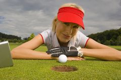Portrait of a mid adult woman lying on grass and smiling. Portrait of a mid adult woman lying on a golf course in front of a golf ball beside a hole Stock Photography