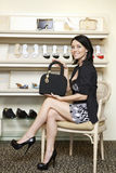 Portrait of a mid adult woman showing designer handbag in footwear store Royalty Free Stock Images