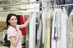 Portrait of a mid adult woman standing by clothing rack Royalty Free Stock Images