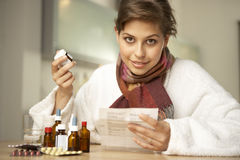 Portrait of a mid adult woman surrounded by tablets and medicine. Royalty Free Stock Photo