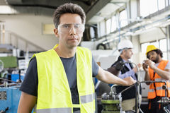 Portrait of mid adult worker wearing protective eyewear with colleagues in background at industry royalty free stock images