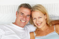 Portrait of mid age couple. On bed smiling to camera Stock Image