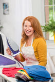 Portrait of mid aged foxy woman with iron. Female busy with housework routine ironing Stock Photography