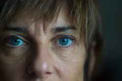 Portrait of mid aged woman with blue eyes, close up and selective focus on one eye, very shallow depth of field. Dark setting, ton