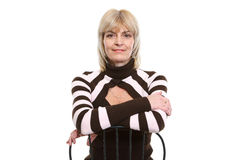 Portrait of middle age woman sitting on chair Stock Photos