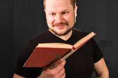 Portrait of middle-aged bearded man reading book Stock Images
