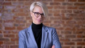 Portrait of middle-aged blonde short-haired woman in glasses smiling into camera and nodding on bricken wall background. stock footage