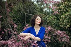 Portrait of a middle-aged brunette in a blue dress next to a cherry blossom stock photography