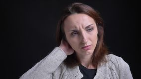 Portrait of middle-aged brunette caucasian woman having terrible headache on black background. Portrait of middle-aged brunette caucasian woman having terrible stock video