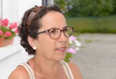 Portrait of a middle-aged brunette woman with eyeglasses, outdoo Stock Photo