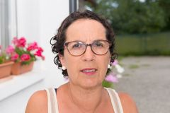 Portrait of a middle-aged brunette woman with eyeglasses, outdoo Stock Images