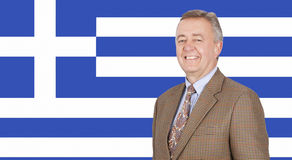 Portrait of middle-aged businessman smiling over Greek flag Stock Photos