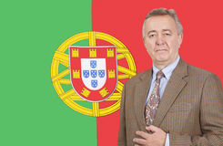 Portrait of middle-aged businessman standing over Portuguese flag Royalty Free Stock Photo